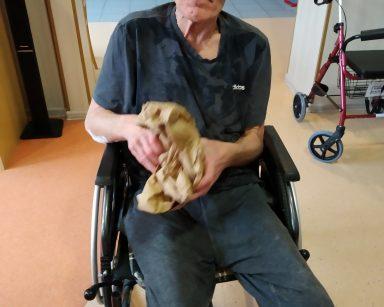Na czarnym wózku inwalidzkim siedzi uśmiechnięty senior. W lekko uniesionych rękach zgniata arkusz brązowego papieru