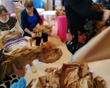 Na pierwszym planie widać ręce gniotące brązowy papier. Ręce należą do jednej z osób, które siedzą w kręgu i zmieniają brązowe arkusze w wielkanocne dekoracje. Widać dwie siedzące seniorki i seniora oraz stojącą neurologopedkę Annę Szmaję-Wysocką