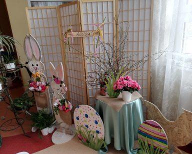 Dekoracja świąteczna: dwa drewniane zające trzymają bukiety kolorowych kwiatów. Obok dwie kolorowe pisanki i kura wykonane z drewna. Z tyłu stolik z różowymi kwiatami, baziami i gałązkami brzozowymi w wazonach