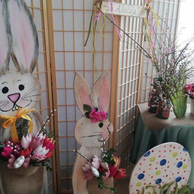 Dekoracja świąteczna: dwa drewniane zające trzymają bukiety kolorowych kwiatów. Przy nich kolorowa drewniana pisanka. Obok stolik z różowymi kwiatami, baziami i gałązkami brzozowymi w wazonach
