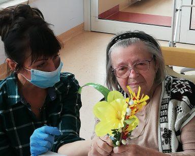 Przy stole siedzi seniorka. W rękach trzyma palmę z żółtym kwiatem. Obok niej siedzi terapeutka Anna Rzepczyńska