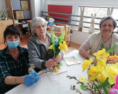 Przy stole siedzi terapeutka Anna Rzepczyńska. W rękach trzyma gałązkę bazi. Obok siedzą dwie uśmiechnięte seniorki. Trzymają w rękach palmy wielkanocne. Na stole dekoracja z żółtych żonkili, bazi i papierowych ozdób