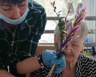 Terapeutka Anna Rzepczyńska trzyma w ręce wielkanocną palemkę i nachyla się nad seniorką. Seniorka wybiera ozdoby do dekoracji palemki
