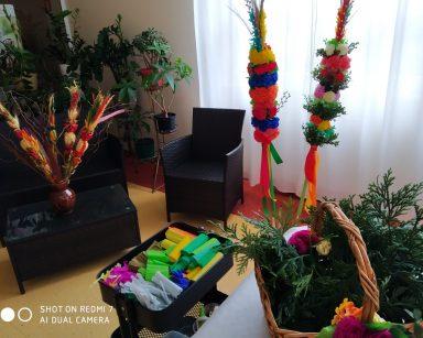 Dekoracje świąteczne: kosz kolorowej bibuły, kolorowe palemki stojące w wazonie, kosz z zielonymi gałązkami, dwie wysokie palmy stojące na podstawce. Palmy są wykonane z kolorowych papierowych kwiatów i zielonych gałązek bukszpanu