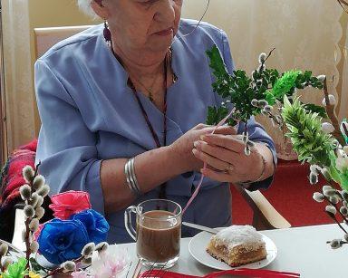 Przy stole siedzi seniorka. Robi palemkę z gałązek bazi i bukszpanu. Przed nią na stole stoi szklanka z kawą, talerzyk z ciastem, kolorowe papierowe kwiaty, wstążki i gotowe palemki