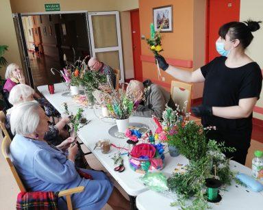 Seniorzy siedzą przy stole. Przygotowują palmy z papierowych kwiatów, świeżych gałązek bazi i bukszpanu. Przy nich stoi instruktorka terapii zajęciowej Małgorzata Jancelewicz. W ręce trzyma palmę wielkanocną