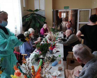 Seniorzy siedzą przy stole. Przygotowują palmy z papierowych kwiatów, świeżych gałązek bazi i bukszpanu. Z jednej strony stołu stoi instruktorka terapii zajęciowej Małgorzata Jancelewicz. Z drugiej kierownik Ilona Gajewska. W rękach trzyma palmę wielkanocną