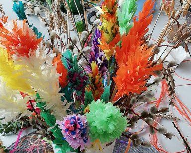 Na stole stoi biały wazon z wielkanocnymi palmami. Palmy wykonane są z kolorowego papieru, gałązek bazi i bukszpanu