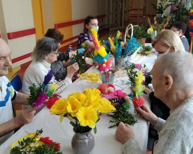 Seniorzy siedzą przy stole. Przygotowują wielkanocne palmy z bibuły, sztucznych kwiatów, świeżych gałązek bazi i bukszpanu. Wraz z nimi pracują fizjoterapeutka Martyna Józefczyk i neurologopedka Anna Szmaja-Wysocka