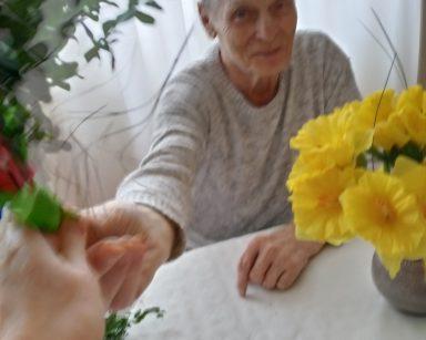 Senior siedzi przy stole. Uśmiecha się i wyciąga rękę z kawałkiem zielonej bibuły. Przed nim, na stole dekoracja z żółtych żonkili