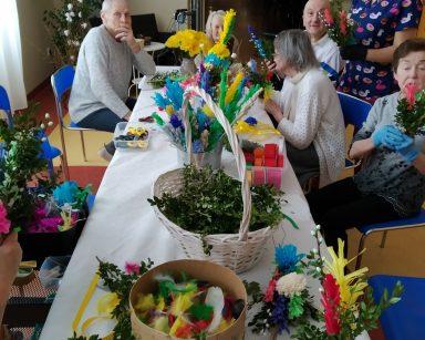 Seniorzy siedzą przy stole. Przygotowują wielkanocne palmy z bibuły, sztucznych kwiatów, świeżych gałązek bazi, kolorowych piórek i bukszpanu. Koło nich stoi fizjoterapeutka Martyna Józefczyk. W rękach trzyma wielkanocna palemkę