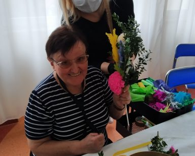 Przy stole siedzi uśmiechnięta seniorka. W ręku trzyma wielkanocną palmę. Przy niej stoi neurologopedka Anna Szmaja-Wysocka. Na stole leżą zielone gałązki i kolorowe piórka