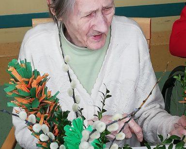 Przy stole siedzi seniorka. W rękach trzyma gałązki na palmę. Na blacie stoi wazon z wielkanocnymi palmami. Palmy wykonane są z kolorowej bibuły, gałązek bazi i bukszpanu