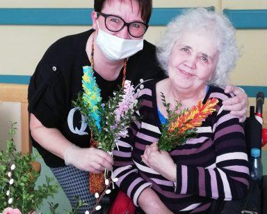 Przy stole siedzi uśmiechnięta seniorka. W ręku trzyma wielkanocną palmę. Koordynatorka wolontariatu Edyta Życzyńska obejmuje ją ramieniem. W drugiej ręce trzyma kolorowe palmy. Na stole leżą zielone gałązki i kwiaty