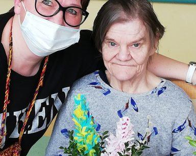 Przy stole siedzi uśmiechnięta seniorka. W ręku trzyma wielkanocną palmę. Koordynatorka wolontariatu Edyta Życzyńska obejmuje ją ramieniem