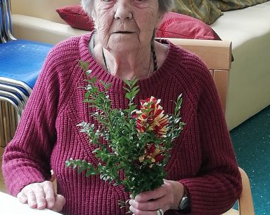 Przy stole siedzi uśmiechnięta seniorka. W ręce trzyma wielkanocną palmę z bukszpanu i kolorowej bibuły