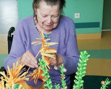 Przy stole siedzi uśmiechnięta seniorka. Robi wielkanocną palmę z kolorowego papieru. Przed nią na stole papierowe dekoracje