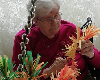 Przy stole siedzi uśmiechnięta seniorka. Robi wielkanocną palmę z kolorowego papieru. Przed nią na stole papierowe dekoracje i gałązki bazi