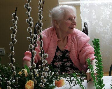 Przy stole siedzi uśmiechnięta seniorka. W ręce trzyma gałązki bukszpanu. Przed nią na stole papierowe dekoracje, wazon z gałązkami bazi, bukszpanem i kwiatami