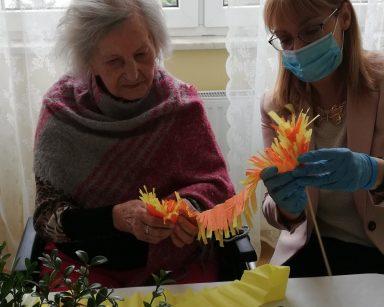 Przy stole siedzi seniorka i dyrektor Agnieszka Cysewska. Wspólnie robią wielkanocną palmę z kolorowej bibuły. Przed nimi dekoracje z bukszpanu, kolorowych kwiatów i gałązek bazi