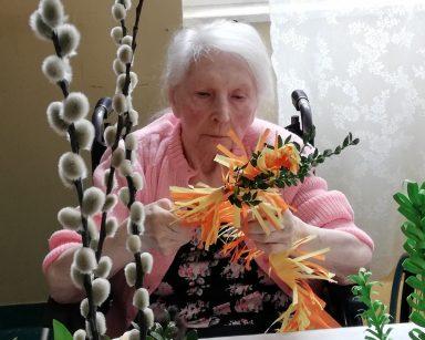 Przy stole siedzi uśmiechnięta seniorka. Robi wielkanocną palmę z kolorowego papieru i bukszpanu. Przed nią na stole papierowe dekoracje, gałązki bazi i bukszpanu