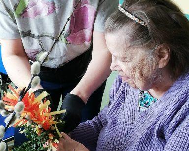 Seniorka siedzi przy stole. Nad nią pochyla się terapeutka Ewa Rodziwiecz. Wspólnie robią wielkanocną palmę z bukszpanu, bazi i kolorowej bibuły