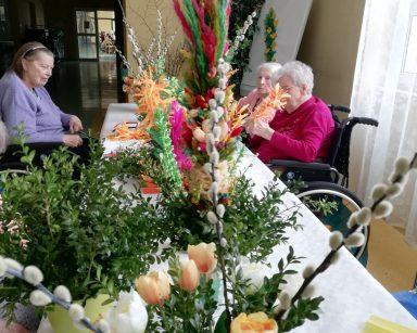 Przy stole siedzą seniorki. Przygotowują wielkanocne palmy z papierowych kwiatów, gałązek bazi i bukszpanu