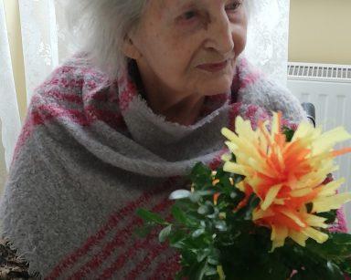 Seniorka siedzi i uśmiecha się. W ręce trzyma wielkanocną palmę z bukszpanu i kolorowej bibuły