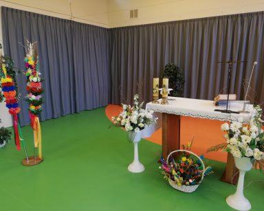 Na sali stoi ołtarz przygotowany na Niedzielę Palmową. Jest nakryty białym obrusem. Obok widać wazony z białymi kwiatami oraz kolorowe wielkanocne palmy