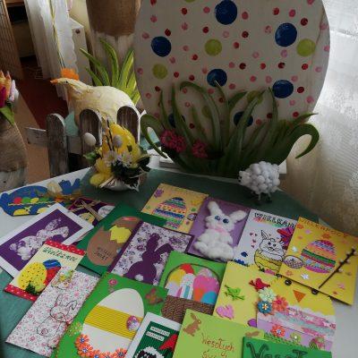 Na stole leżą rozłożone kartki świąteczne. Są ozdobione obrazkami wielkanocnych zajączków, baranków, pisanek, kwiatów i bazi. Na blacie widać jeszcze białego baranka i żółty stroik. Obok stołu stoją drewniane dekoracje: pomalowana na żółto kura, duża biała pisanka w niebieskie zielone i różowe kropki, tabliczka z napisem Alleluja!