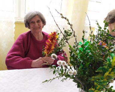 Przy stole siedzi uśmiechnięta seniorka. W ręku trzyma wielkanocną palmę z bukszpanu i kolorowej bibuły. Na stole stoi wazon z bukszpanem i palemkami