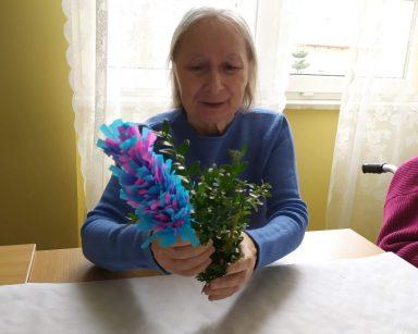 Przy stole siedzi uśmiechnięta seniorka. W rękach trzyma wielkanocną palmę z bukszpanu oraz palmę z kolorowej bibuły