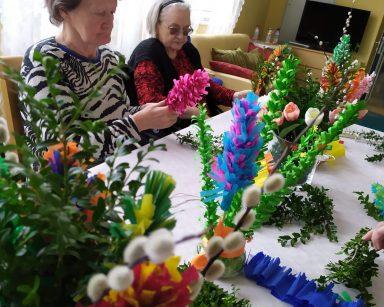 Przy stole siedzą seniorki. Przygotowują wielkanocne palmy z kolorowej bibuły, gałązek bazi i bukszpanu