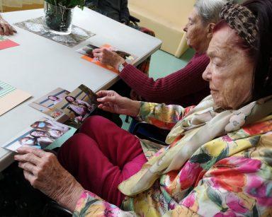 Przy stole siedzą dwie seniorki. Oglądają swoje fotografie.