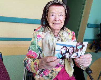 Seniorka uśmiecha się szeroko. W dłoniach trzyma swoje zdjęcie.