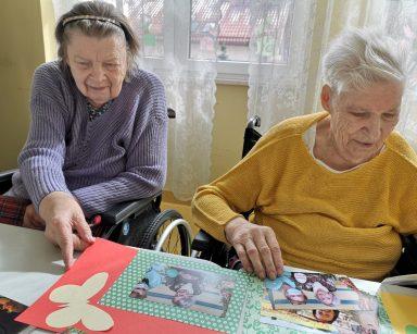 Dwie seniorki siedzą przy stole. Oglądają zdjęcia.