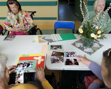 Cztery seniorki siedzą przy stole. Oglądają fotografie.