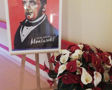 Na stelażu widać podpisany portret Stanisława Moniuszki. Obok stoi wazon z bukietem białych i czerwonych kwiatów anturium.