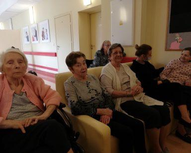 Na korytarzu siedzą seniorki i psycholożka Maria Skubich-Wiczling. Czekaja na rozpoczęcie transmisji koncertu.