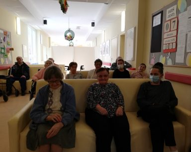 Na korytarzu siedzą seniorzy oraz pracownicy: terapeutka zajęciowa Magdalena Poraj-Górska i psycholożka Maria Skubich-Wiczling. Czekaja na rozpoczęcie transmisji koncertu.