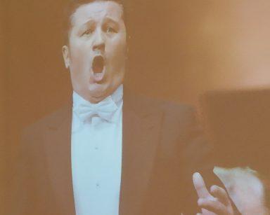 Pan Piotr Beczała śpiewa. Ma na sobie galowe ubranie: białą koszulę z białą muszką oraz czarny frak.