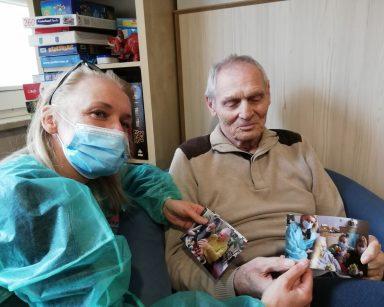 Kierownik Ilona Gajewska i senior oglądają wspólnie zdjęcia. Zdjęcia przedstawiają seniora podczas przygotowań do Wielkanocy.