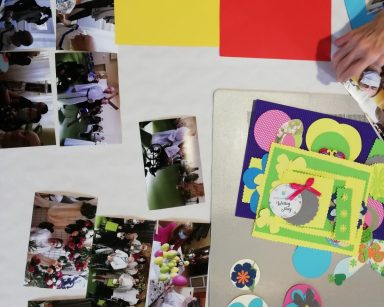 Na blacie leżą rozłożone zdjęcia mieszkańców, obok widać kolorowe kartki, kokardki, wycięte motylki oraz barwne papierowe kwiaty do dekoracji.