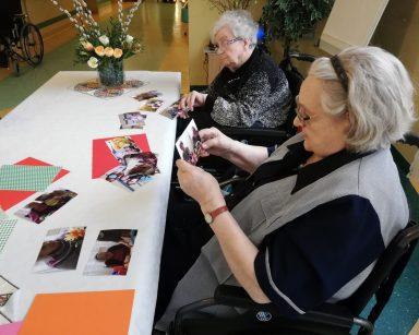 Przy stole siedzą dwie seniorki. Oglądają zdjęcia, które trzymają w rękach. Przed nimi na blacie leżą rozłożone zdjęcia z przygotowań do Wielkanocy.