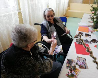 Na stole stoją wazony ze świątecznymi dekoracjami: baziami i tulipanami. Na blacie widać rozłożone zdjęcia z przygotowań do Wielkanocy. Przy stole siedzą dwie seniorki. Rozmawiają i wymieniają się zdjęciami.