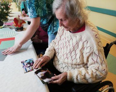 Na pierwszym planie widać seniorkę. Siedzi przy stole i ogląda swoje zdjęcia z przygotowań do Wielkanocy. W tle widać innych pracowników i seniorów.