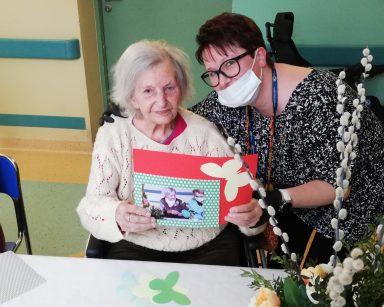 Koordynatorka wolontariatu Edyta Życzyńska siedzi przy stole i obejmuje seniorkę. Seniorka uśmiecha się. W rękach trzyma swoje zdjęcie na ozdobnej papierowej kartce.
