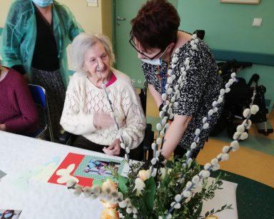 Koordynatorka wolontariatu Edyta Życzyńska rozmawia z seniorką. Obydwie się śmieją. Przed nimi na blacie leży zdjęcie z przygotowań do Wielkanocy. Zdjęcie jest w ozdobnej papierowej ramce.