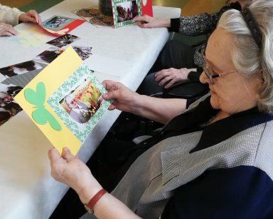 Dwie seniorki siedzą przy stole. Każda z nich trzyma swoje zdjęcie. Zdjęcia są przyklejone na kolorowe kartki i udekorowane papierowymi ozdobami.