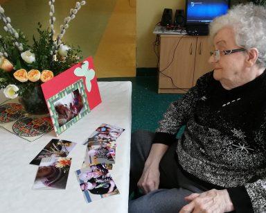 Seniorka siedzi przy stole. Przed nią na blacie leżą zdjęcia z przygotowań do Wielkanocy. Seniorka patrzy na swoje zdjęcie oparte o wazon z kwiatami. Zdjęcie ma ozdobna ramkę z kolorowego papieru.